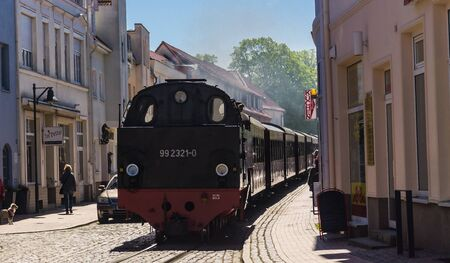BAD DOBERAN, GERMANY - May 13, 2019 - steam locomotive Molli pulling coaches through the narrow streets of Bad Doberan Sajtókép