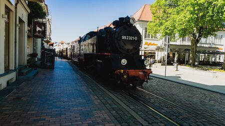 BAD DOBERAN, GERMANY - MAY 13, 2019 - Molli steam locomotive pulling coaches through the narrow streets of Bad Doberan 02
