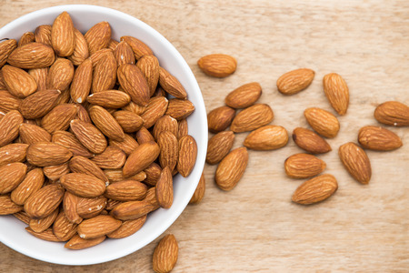 Almonds in a white cup rests on a wooden table