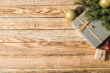 Composición navideña. Regalo de Navidad. Bola navideña. piñas. ramas de abeto sobre fondo de madera vista superior. Foto de archivo