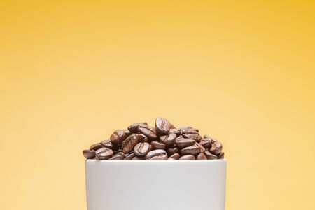 Coffee beans in white cup isolated on yellow background Banque d'images