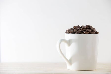 Coffee beans in white cup isolated on white background