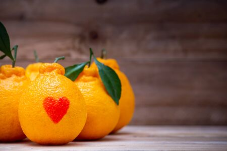 Oranges have a red heart-shaped put on the wooden table.