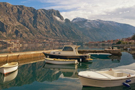 Fishing boats in Bay of Kotor on a winter day with  the Lovcen mountain in the background. Prcanj town, Montenegro