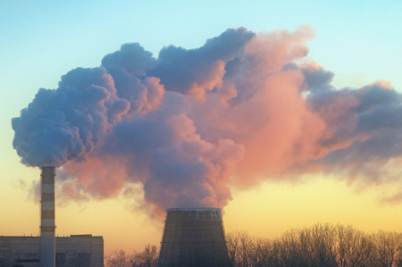 Smoke from two factory chimneys in the light of the setting sun. Ryazan city, Russia