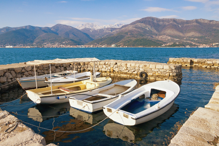 Fishing boats in the small harbor after the storm. Bay of Kotor, Montenegro, winter