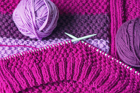 Hobby concept.  Unfinished needlework with balls of wool and knitting  needles Stock Photo