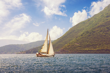 Sailboat sails  near shore of Bay of Kotor (Adriatic Sea) on a beautiful sunny day. Montenegro. Travel concept
