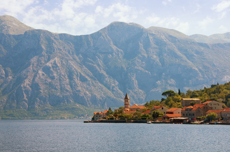Beautiful Mediterranean landscape with a small seaside village in the background of the mountains. Montenegro, Adriatic Sea. View of Bay of Kotor and Stoliv village Stock Photo