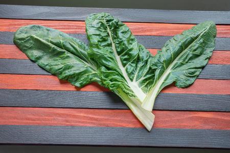 Blitva ( chard leaves ) - popular leafy vegetables in Balkan cuisine. Striped rustic background