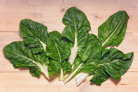 Blitva ( chard leaves ) - popular leafy vegetables in Balkan cuisine. White rustic background, flat lay
