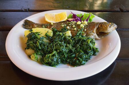 Balkan cuisine. Grilled fish ( trout  ) with leafy green vegetables on white plate. Dark rustic background Фото со стока