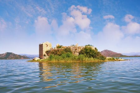 View of Lake Skadar - the largest lake in the Balkans - and the ruined fortress of Grmozur on a small island. Montenegro