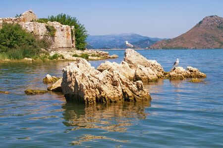 Picturesque lake with a ruined fort on a small island. View of Lake Skadar - the largest lake in the Balkans - on sunny summer day. Fortress Grmozur. Montenegro Stockfoto