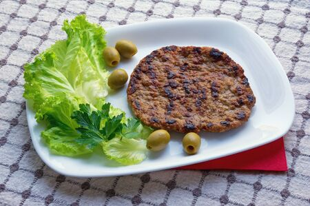 Balkan cuisine. Pljeskavica - grilled dish of minced meat - with green olives and leaves of lettuce on white plate Stockfoto