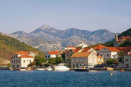 Beautiful autumn Mediterranean landscape. Small seaside village with red roofs at the foot of the mountains. Montenegro, Adriatic Sea, Bay of Kotor, Lepetane village