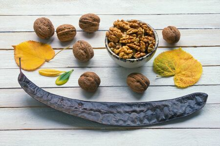 Autumn. Whole walnuts, walnut kernels, yellow leaves and pod of gleditsia tree on white rustic background