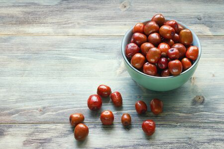 Jujube fruits  ( Ziziphus jujuba ) in bowl on rustic background. Free space for text