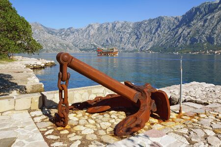 Old rusty anchor on coast of  Kotor Bay on sunny autumn day. Montenegro, Adriatic Sea, Prcanj town