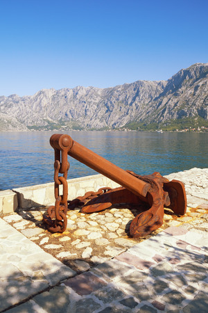 Old rusty anchor on coast of Bay of Kotor on sunny day. Montenegro, Adriatic Sea, Prcanj town Stockfoto