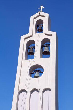 White bell tower of Orthodox church against blue sky.  Montenegro. Church of St. Peter of Cetinje ( Svetog Petra Cetinjskog ) in Prcanj town