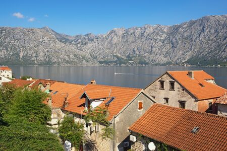 Sunny Mediterranean landscape. Montenegro, Adriatic Sea. View of Bay of Kotor and red roofs of ancient town of Prcanj