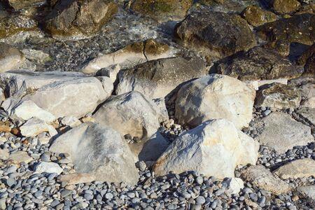 Wet and dry stones and pebbles on the coastline, background. Montenegro, Adriatic Sea Stockfoto