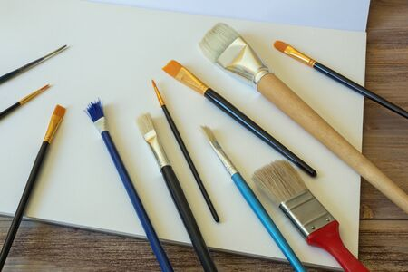 Different types of  brushes for painting on sheet of white paper
