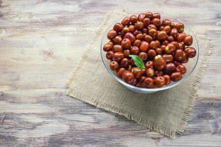 Jujube fruits  ( Ziziphus jujuba ) in glass bowl on rustic background. Free space for text
