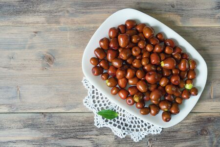 Jujube fruits  ( Ziziphus jujuba ) on white plate on rustic background. Free space for text