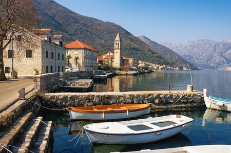 Small Mediterranean village against mountains. Montenegro, Adriatic Sea. View of Bay of Kotor and Stoliv village on sunny winter day