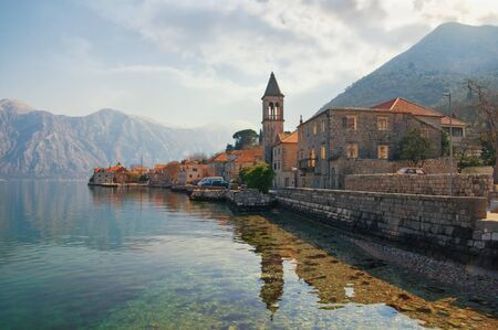 Beautiful mediterranean landscape. Small seaside village, clouds and mountains are reflected in water. Montenegro, Adriatic Sea. View of Bay of Kotor and Stoliv village on sunny winter day