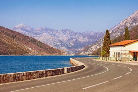 Sharp turn of road. Adriatic Highway (Jadranska magistrala) on sunny winter day. Montenegro, Kotor Bay 写真素材