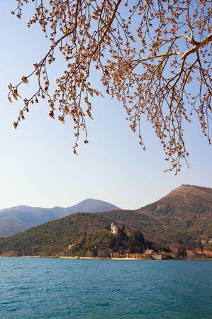 Springtime. Beautiful Mediterranean landscape on sunny day.  Montenegro, Adriatic Sea, Bay of Kotor,  view of Kamenari village with Church of Sveta Nedjelja and brances of White Walnut tree ( Juglans