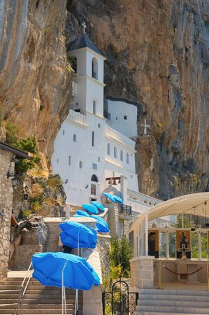 Religious architecture.  Ostrog monastery, located in an almost vertical rock. View of road to temple with blue sun umbrellas on sunny day. Montenegro 写真素材
