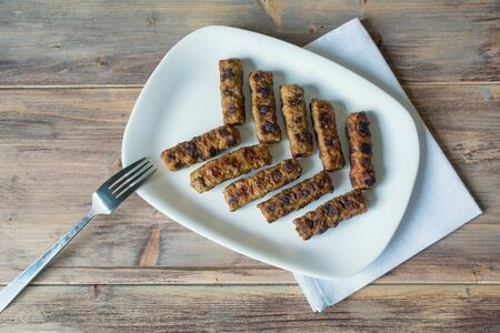 Balkan cuisine. Cevapi - grilled dish of minced meat - on white plate.  Rustic background, flat lay, free space for text