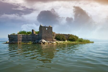 Lake with ruined fort on small island. View of National Park Lake Skadar and Fortress Grmozur. Montenegro