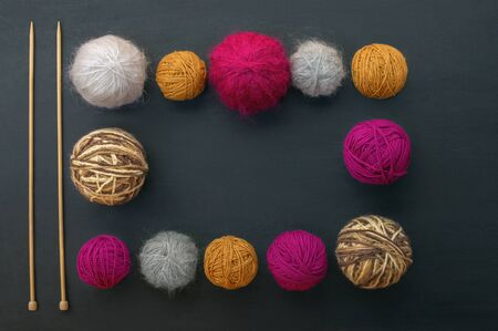 Knitting needles and balls of wool on black table. Flat lay, free space for text