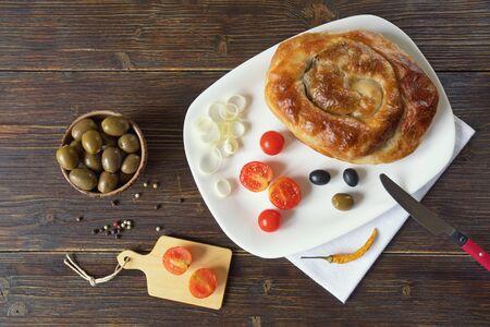 Balkan cuisine. Burek, filled pastries  - popular national dish.  Rustic background, flat lay. Free space for text 写真素材
