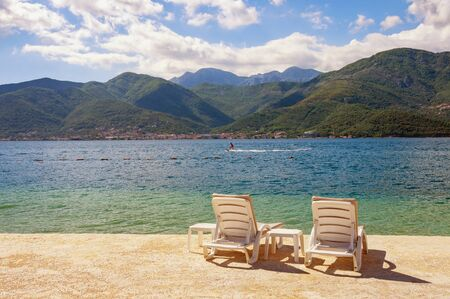 Summer vacation. Beautiful sunny landscape with two chaise lounges on beach. Montenegro, Adriatic Sea, view of Bay of Kotor near Tivat city