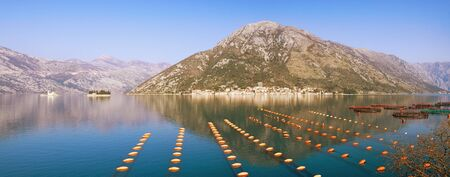 Beautiful Mediterranean landscape with fish farm on sunny winter day. Montenegro, Adriatic Sea, Bay of Kotor. Perast town and two small islands in the distance