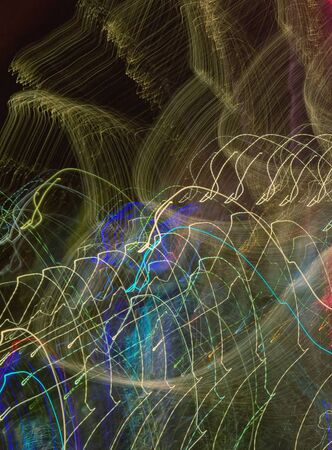 Motion - abstract background. Rhythmic colorful lines in dark - road lights from moving car at night. Slow shutter speed 写真素材