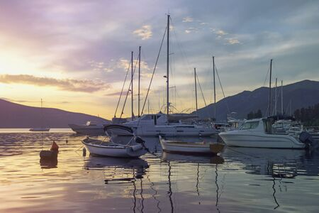Sunset. Beautiful Mediterranean landscape with boats on water. Montenegro, Adriatic Sea. View of Bay of Kotor near Tivat city. Toning
