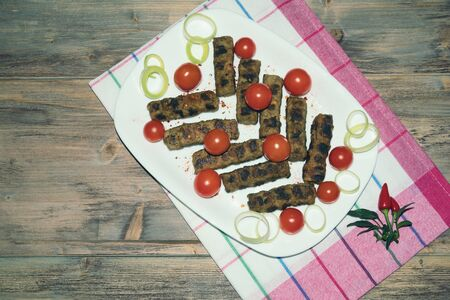Balkan cuisine. Cevapi - grilled dish of minced meat.  Rustic background, flat lay, free space for text