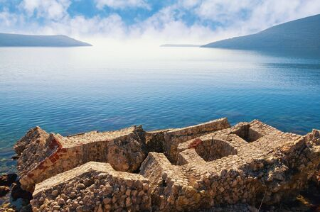 Concept of collapsing, disasters. Wall of a stone building in the sea.  Montenegro, Herceg Novi city. Ruins of  Citadel fortress (Mezzaluna) destroyed by an earthquake 写真素材