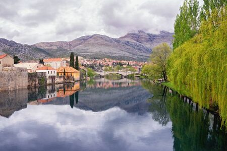Cloudy spring day. Clouds, mountains, green trees and town are reflected in water of river. Bosnia and Herzegovina. View of Trebisnjica river and Old Town of Trebinje
