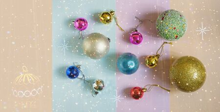 Bright Christmas balls of different sizes on the background of colored paper and garland of lights. Flat lay, free space for text