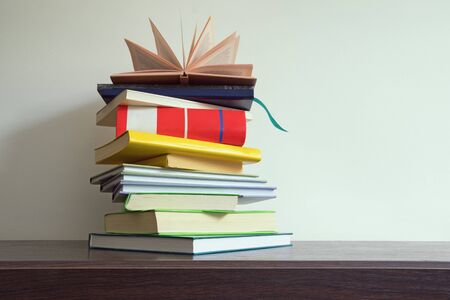 Stack of books of different sizes and colors on the table, free space for text 写真素材