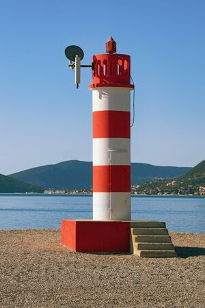 Red and white striped beacon. Coast of Bay of Kotor ( Adriatic Sea ) on sunny winter day. Montenegro, Tivat 写真素材