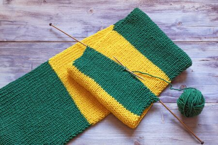 Knitting. Striped yellow-green scarf with knitting needles and ball of wool on rustic background